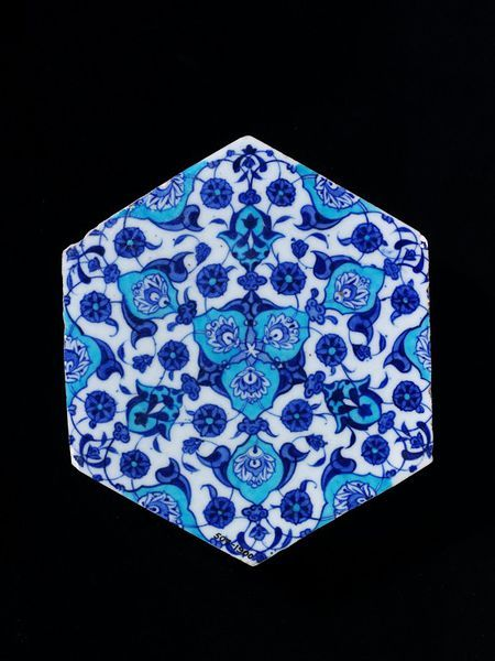 Tile | Made in Iznik, Turkey, ca. 1525-1550 | Materials: fritware, underglaze painted in cobalt blue and turquoise, glazed | Tile of glazed grey fritware, painted in dark blue and turquoise-blue on a white slip. Hexagonal in shape and painted with a symmetrical design of palmettes, arabesques and flowers on interlaced leafy stems | VA Museum, London