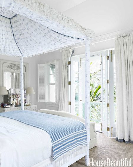"The focal point of the master bedroom is the sumptuous bed, designed by Alberto Pinto and purchased through Christie's Auction, NYC: ""It's serious enough to carry the room, yet crisp and breezy,"" says designer, Amanda Lindroth. When the doors are open, "",,,we fall asleep to the sea breeze blowing through the palms."""