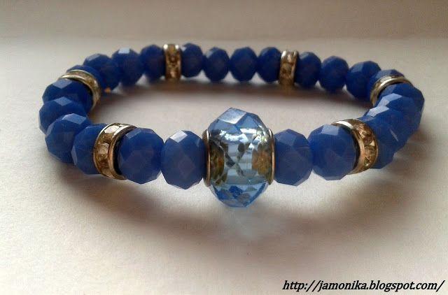 Niebieska bransoletka wykonana ze szklanych koralików fasetowanych z metalowymi przekładkami ozdobionymi małymi cyrkonami. Na środku ozdobny niebieski koralik, bransoletka na gumce.