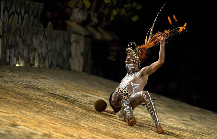 "A Mexican man in pre-hispanic Aztec costume play the ball during a traditional ""Juego de Pelota"" (in Spanish) at the Xcaret eco-park in Xcaret, Mexico on June 5 2009.  Called by the Maya ""pok-ta-pok"" and for the Aztecs ""tlachtli"", it is a former Indo-American game of ball which practice goes back to approximately 3.500 years in the past and has been considered to be a precedent of the football. AFP PHOTO/Luis Acosta (Photo credit should read LUIS ACOSTA/AFP/Getty Images)"