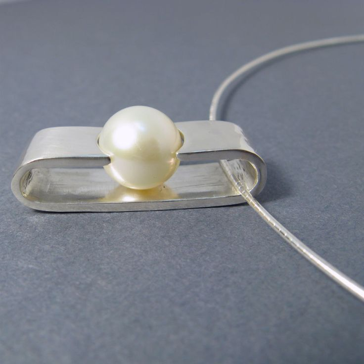Pearl sterling silver necklace  -  sliding white pearl pendant with neck wire by lotusstone. $78.00, via Etsy.