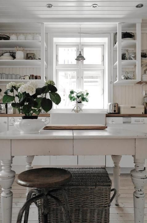 Wood on the ceiling helps add character to an all white cottage kitchen.