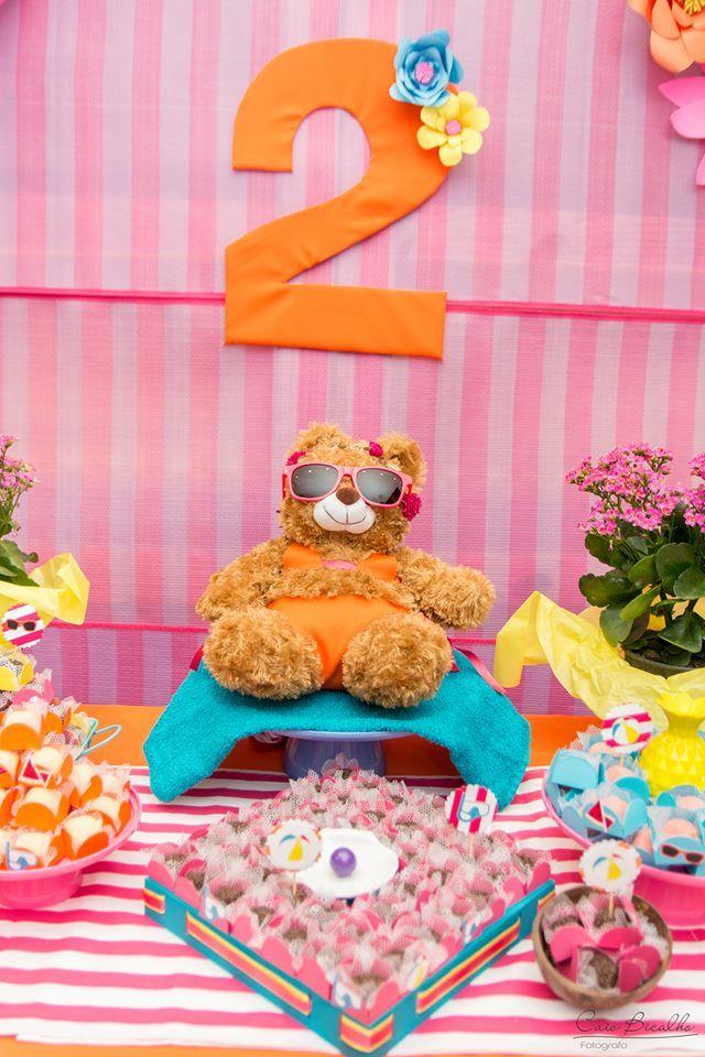 Detalhe de mesa de aniversário menina com o tema praia. Uma ursa foi vestida com biquini e as toalhas laranja e pink com enfeites amarelo e azul turquesa deixaram essa mesa do bolo de aniversário de dois anos ainda mais colorida.