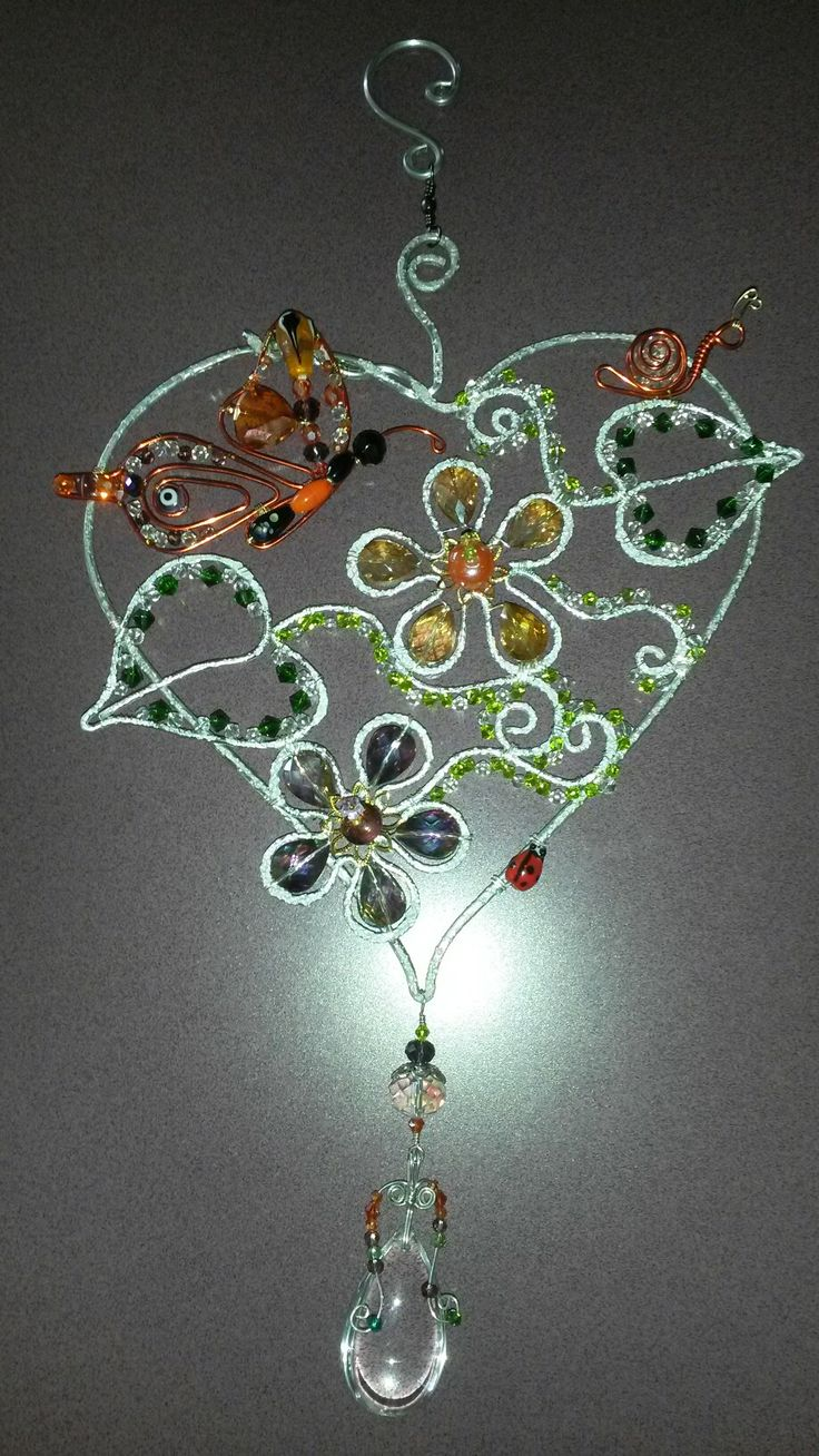 Wire wrapped beaded sun catcher with butterfly and flowers.