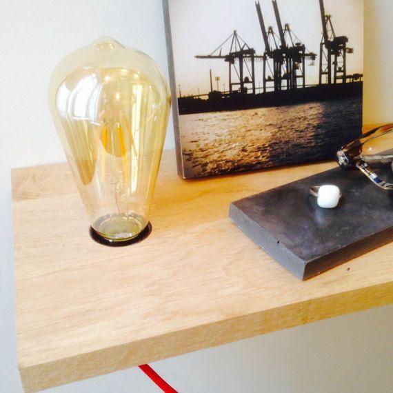 Cette tablette suspendue en bois de chêne avec sa lampe intégrée apportera style et légèreté à votre chambre. Très pratique, vous pouvez y poser vos livres, lunettes, bijoux pour la nuit. Aussi, sa lampe est équipée dun interrupteur, ce qui vous permettra de lallumer ou de léteindre sans bouger de votre lit. Cette tablette est réalisée en chêne clair provenant dun forêt labellisée PEFC. Le cordon électrique recouvert dun tissu rouge mesure 2m. La douille est de type E27. Nous vous…
