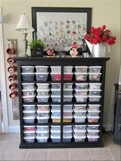 An old dresser, without the drawers organized with plastic shoe boxes to hold craft supplies