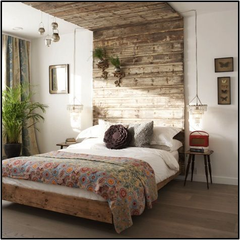 Running the material for your headboard up the wall and even onto the ceiling not only defines the space, it helps thread it together with a common element (Google)