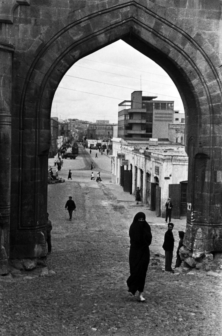 Moslem woman, 1939. View onto Bazaar Street through the fortress gate. Baku constructivism. Palace of the Press Azerneshr building, by architect S. Pen. Baku, Azerbaidjan.