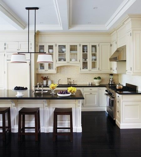 Dark floors in the kitchen give depth to the cream cabinets. Love the color  scheme