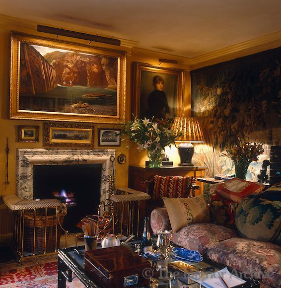 cozy sitting room in a London townhouse are decorated with gilt-framed paintings and a large tapestry ~ Mark Birley design