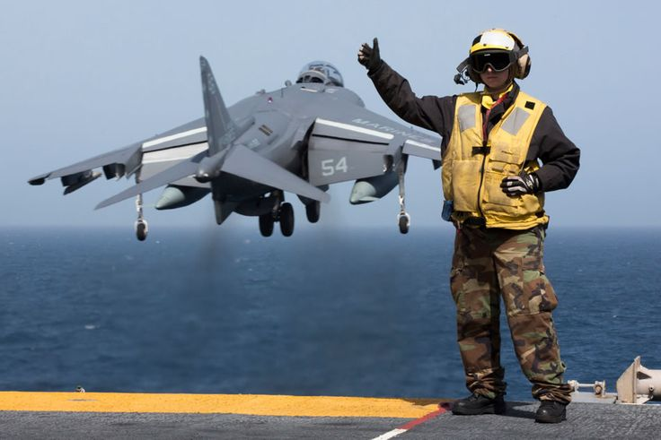 Aviation Boatswain's Mate (Handling) 2nd Class Christiana Marszalek signals as an AV-8B Harrier takes off from the amphibious assault ship USS Kearsarge (LHD 3).