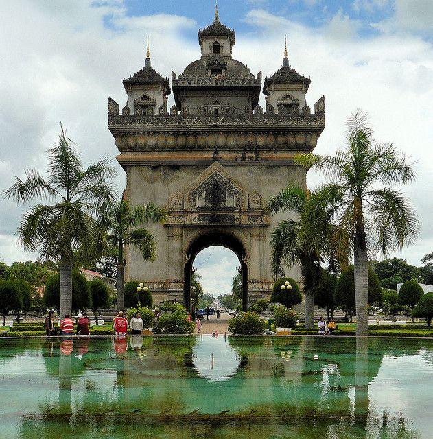 """O Arco do Triunfo de Vientiane, Laos    Curiosidade: É dedicado a todos que lutaram na luta pela independência da França. Embora tendo uma semelhança geral com o Arco do Triunfo, em Paris, é tipicamente do Laos, decorado com muitas figuras Kinnari. Foi construído com recursos americanos, inicialmente destinados a construção um novo Aeroporto, no entanto, o governo construiu o monumento em seu lugar em 1962 ou 1968. .   Situado no Boulevard Lan Xang, conhecido como o """"Champs Elysées do…"""
