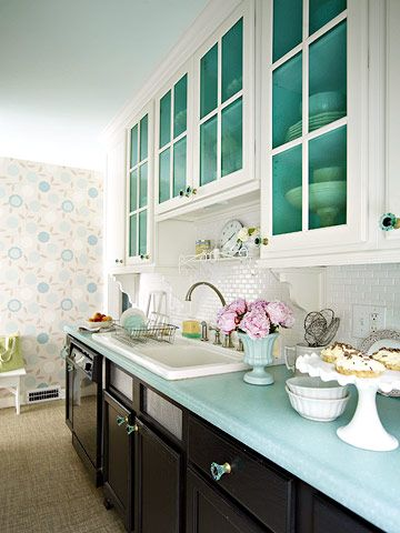 Colorful Kitchen -- Energize a small galley kitchen with color. Painting the interiors of these white, glass-front cabinets gives them a bold new look. Vintage-style glass pulls add bursts of the same turquoise to the cabinetry's exterior. An inexpensive laminate countertop completes the colorful refresh in this simple galley kitchen