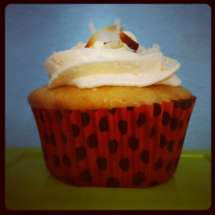 Coconut cake made with coconut water, stuffed with crushed pineapple and topped with buttercream icing and toasted coconut! #cupcake #pinacolada