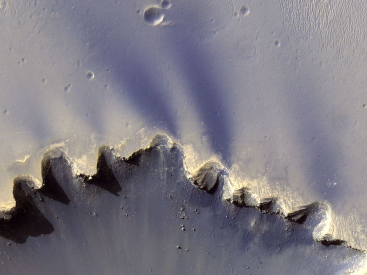 """A piece of Mars: Back in 2007, the Mars Exploration Rover Opportunity spent a great deal of time investigating the rim of Victoria crater. Here is the northern rim of the crater, showing several dark (bluish) sandy streaks formed by the wind as it blows dark sand out of the crater. You can see small dark ripples inside the crater, the source of the dark sand. And if you look very carefully you can see the tracks the rover left behind. (HiRISE PSP_009141_1780)"""
