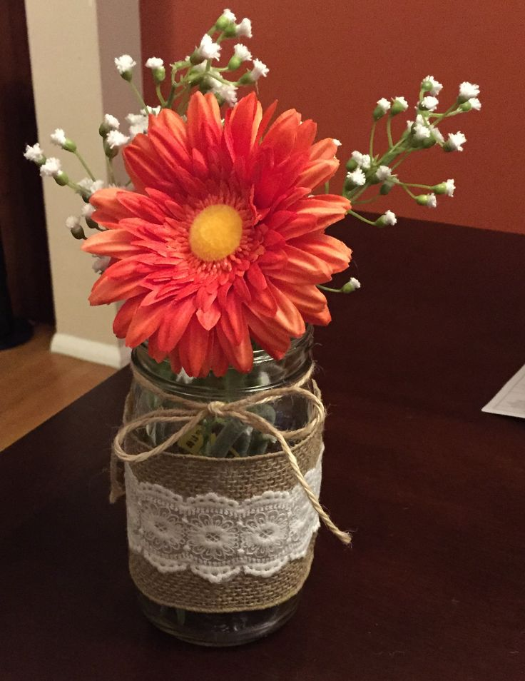 Mason jar, burlap, lace, twine, orange gerbera daisy, baby's breath, wedding reception centerpiece. I made this, but plan to use royal blue jute twine instead of the twine in this picture. Plus I'll actually cut and arrange flowers instead of shoving fake ones in haphazardly...