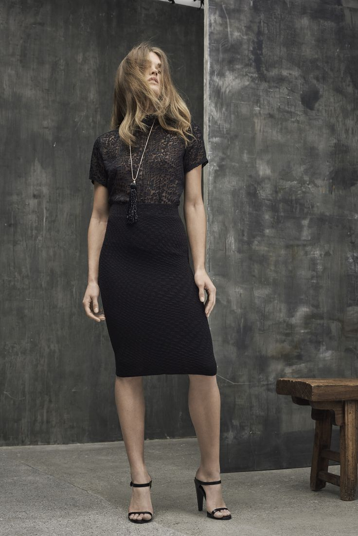 Black shirt with a see through pattern and a midi black skirt.