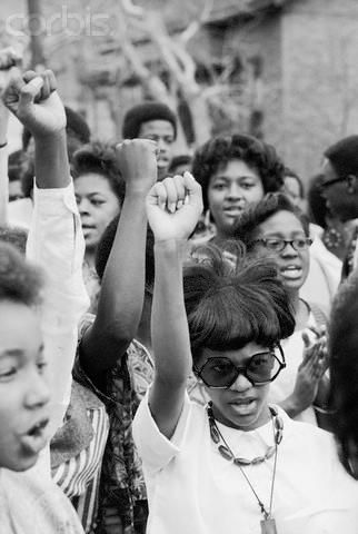 Young women raise their fists in the Black Power salute at a civil rights rally.