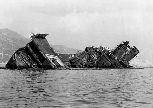 1970s Wreck of RMS Queen Elizabeth just out of the Hong Kong Harbour. My Dad was working for OOCL who was owner of the QE at the time. (Uncle) C.Y. Tung intended to convert her into a floating University cruise ship. In 1972, while undergoing refurbishment in Hong Kong harbour, she caught on fire under mysterious circumstances and was capsized by the water used to fight the fire. In 1973, her wreck was deemed an obstruction, and she was partially scrapped where she lay.