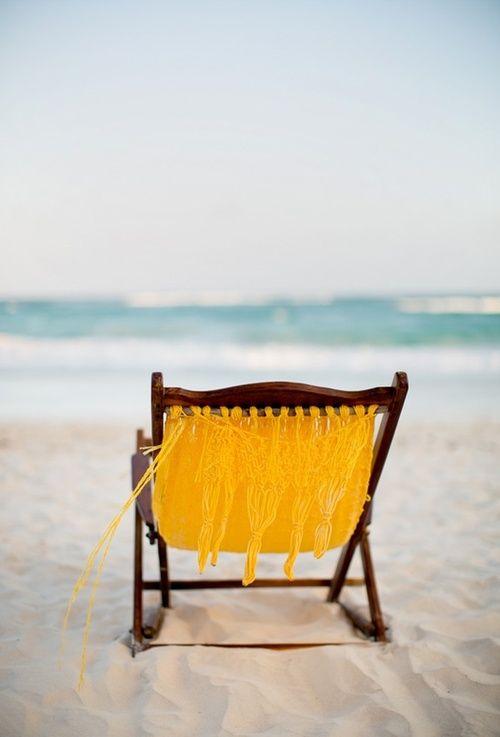 gelber Liegestuhl am weißen Sandstrand.