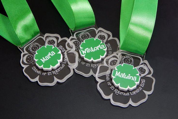 Pamiątka pobytu dziecka w żłobku Medal pamiątkowy wykonany z przezroczystej pleksi z zielono-białą wklejką.