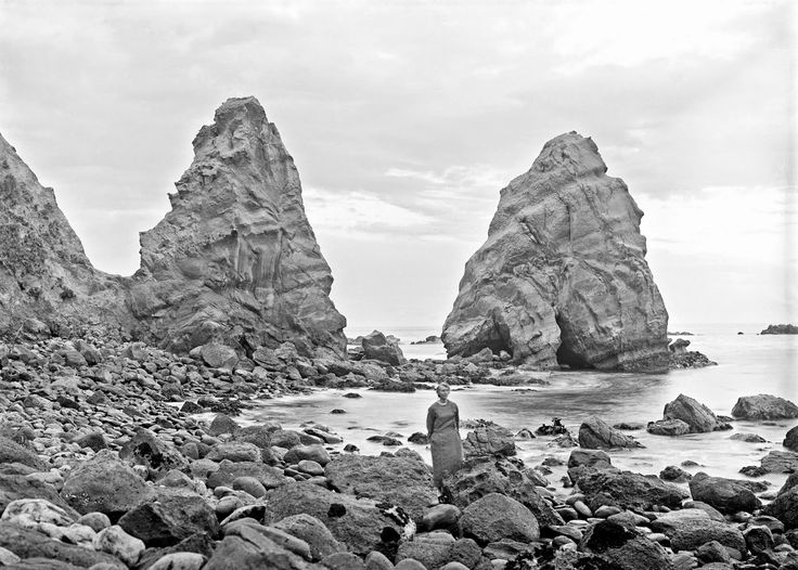 History in Photos: Albert Percy Godber.  The rocks, Huriawa, near Karitane, showing rock formation  at the water's edge. Laura Godber standing in centre foreground, ca. 1925.  New Zealand
