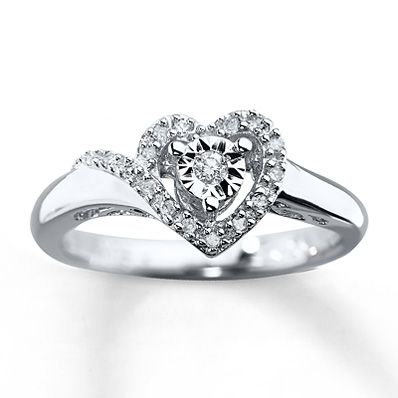 A row of diamonds lovingly creates a heart-shaped frame around a center diamond in this splendid ring for her. This promise ring is crafted in sterling silver and has a total diamond weight of 1/10 carat.