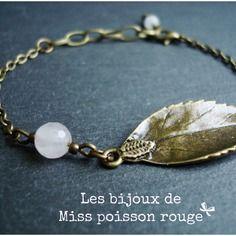 """Bracelet lilou - chaîne et feuille bronze ; jades facettées blanches. Signé """"les bijoux de Miss poisson rouge""""."""