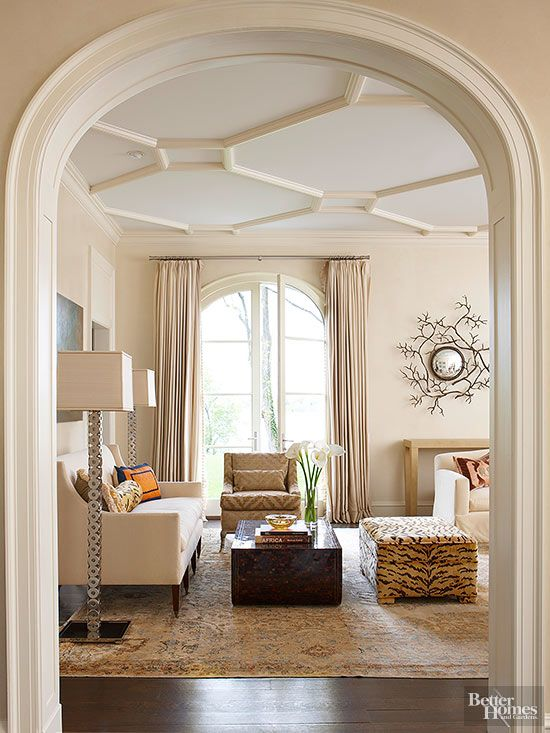 An arched opening leads to a formal living room outfitted with a contemporary mix of furnishings. Here, the classic shape of the simple arch and clean lines of the opening's inset panels take precedence over elaborate carvings. The ceiling displays a geometric painted plaster relief of skewed octagons connected by rectangles.