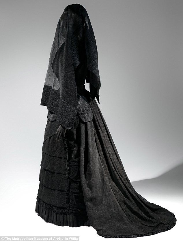 This Victorian-era ensemble (estimated from 1870 to 1872) features the black hue, modest silhouette, and shrouding veil typical of mourning attire at the time