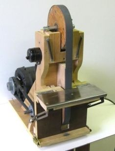 Belt Sander - Homemade belt sander constructed from plywood, pulleys, an electric motor, shafting, springs, steel plate, and a switch.