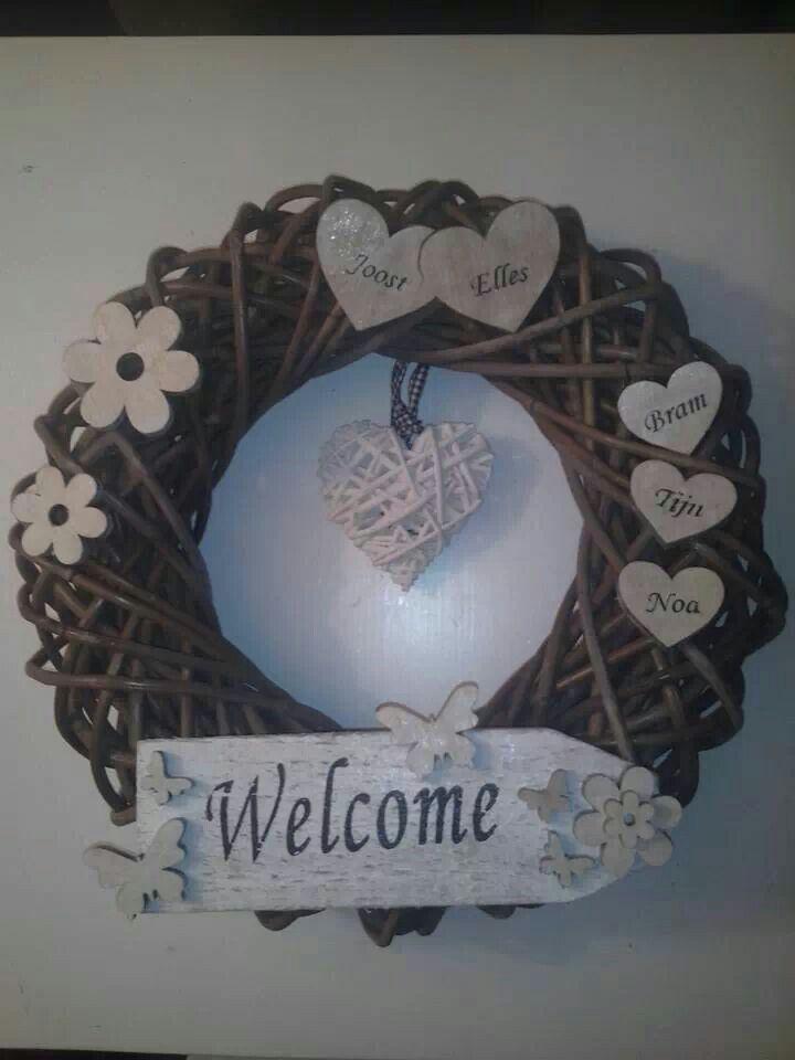 rieten krans versierd met bloemen en harten van hout