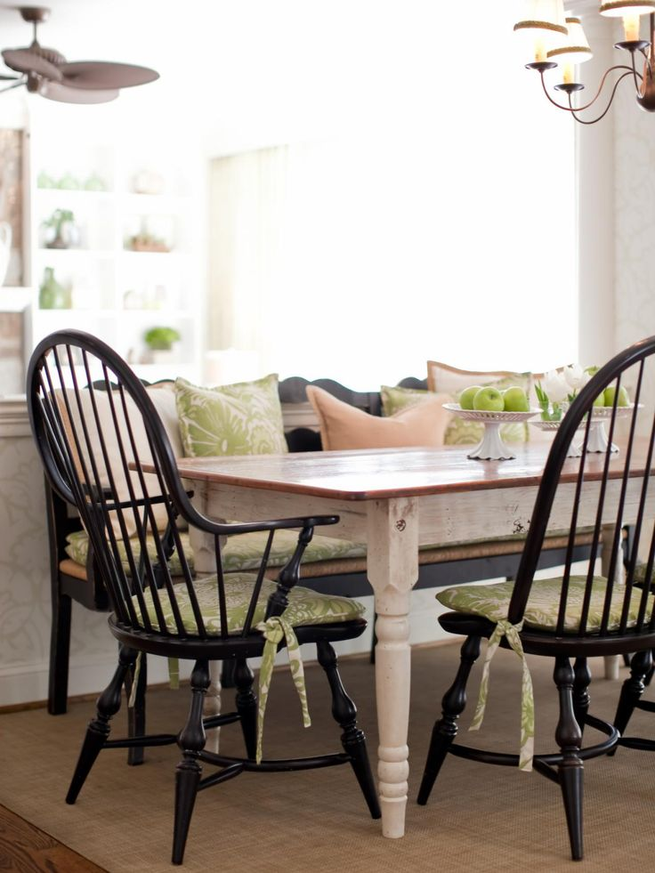 This country dining setting features a farmhouse table with black Windsor chairs and bench to give the space a more causal feel. Green-and-white-pattern cushions pad the seats with matching throw pillows on the bench. Neutral pillows are mixed in complementing the distressed wooden table and neutral rug.