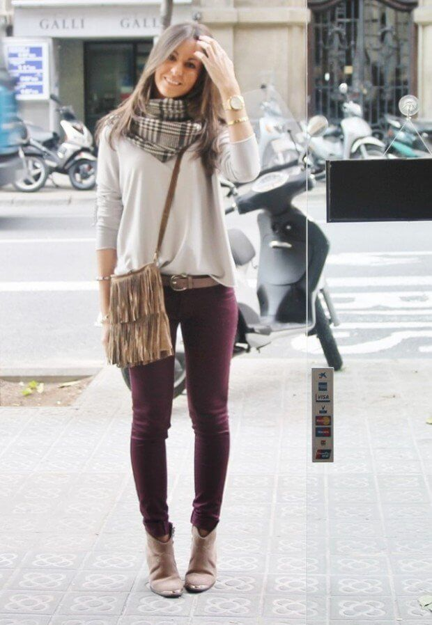 Woman wearing oxblood jeans with a nude top and a plaid scarf