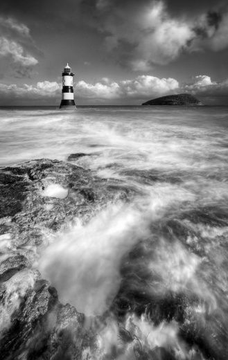 A view over the sea towards Penmon lighthouse and Puffin Island on the north-eastern tip of Anglesey.