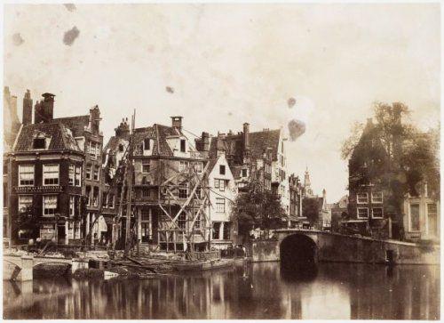 Rokin tijdens de bouw van de nieuwe Langebrug (brug nr. 198) Gezien naar de Langebrugsteeg en de huizen Rokin 121 en 123, dat in de steigers staat. In het midden de Grimnessesluis (vaste brug 202) en rechts daarvan Oude Turfmarkt B44-B45 met in het verschiet de Zuiderkerkstoren. Documenttypefoto VervaardigerBenjamin Brecknell Turner (fotograaf) CollectieCollectie Stadsarchief Amsterdam: foto-afdrukken Datering 17 mei 1857 t/m 3 juni 1857