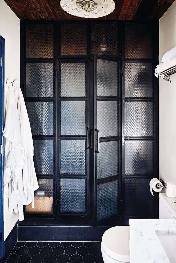 The steam shower is custom-crafted from chicken wire glass, a metal frame, and a light fixture from Luddite Antiques