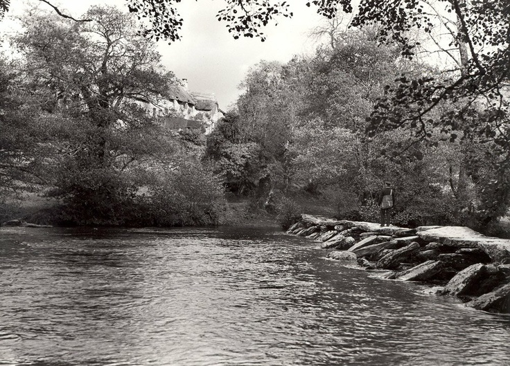 A postman walks along the Tarr Steps, a clapper bridge across the river Barle, Somerset. Tarr Farm can be glimpsed through the trees in the background. Image taken: 1938.