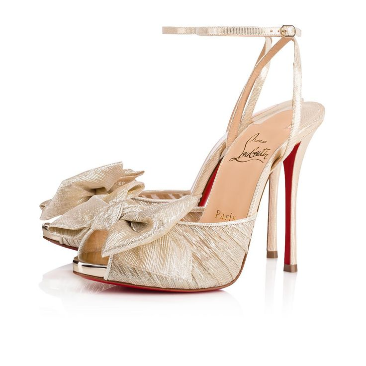 """Christian Louboutin is enamored with bows and how they are used to accentuate the female form. Here at the toe of """"Artydiva"""", a gorgeous hand-tied bow in platinum chiffon lamé casts a feminine spell on this 120mm sandal in luminous specchio leather."""