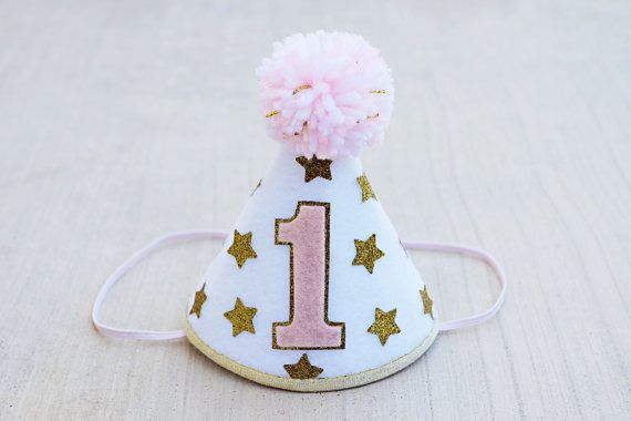 Twinkle Twinkle Little Star…Im over the moon about this new hat!!  It is a stiffened small (cream or white) felt party hat decorated with her birthday number in pink with sparkly gold outline, sparkly gold stars, gold ribbon trim and a speckled yarn pom pom on the top. 1/8 elastic strap. Diameter of hat is 4, and height 5. ** Hat shipped will be first picture in listing unless otherwise noted in comment section. Select gold or silver at checkout. Can even be made for a boy- see last pict...