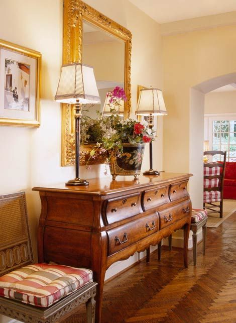 """Interior Designer Charles Faudree: """"French Flair"""". In a more toned down example of his work, Faudree makes a classic first impression in this foyer with a gilt framed mirror, warm wood flooring and furniture, and a tole bucket filled with flowers."""