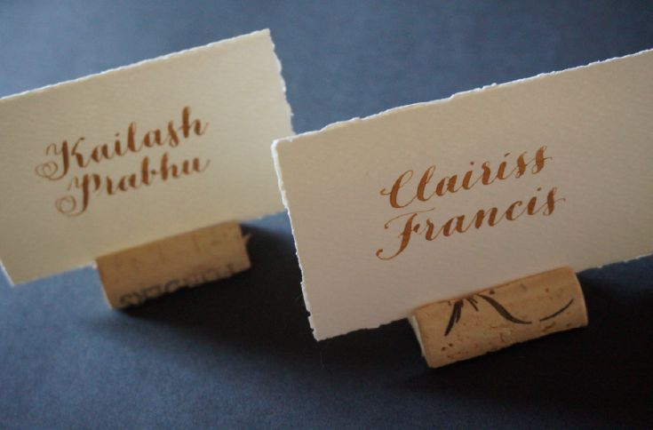Deckled-edged place cards inserted into sliced corks for a wedding held at a vineyard