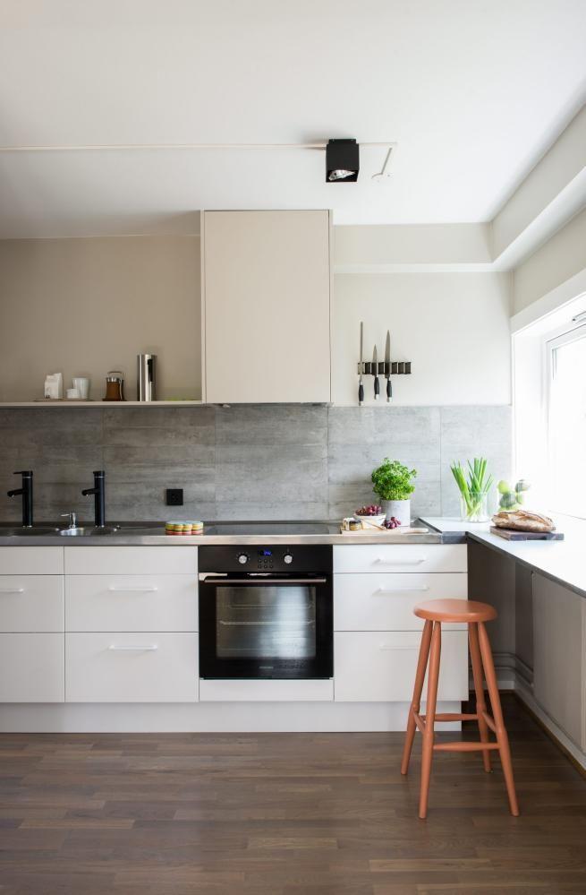 PUSSET OPP MED BRUKT BENKEPLATE: Ikeakjøkkenet er nytt, mens stålbenken er gammel og brukt, og opprinnelig fra et mekanisk verksted i Fredrikstad. Flisene i sprutsonen heter Re-Use Concrete, og er fra Bella Fliser. Veggfargen Soft Sand fra Nordsjö gjør at den hvite innredningen fremstår som ekstra hvit.