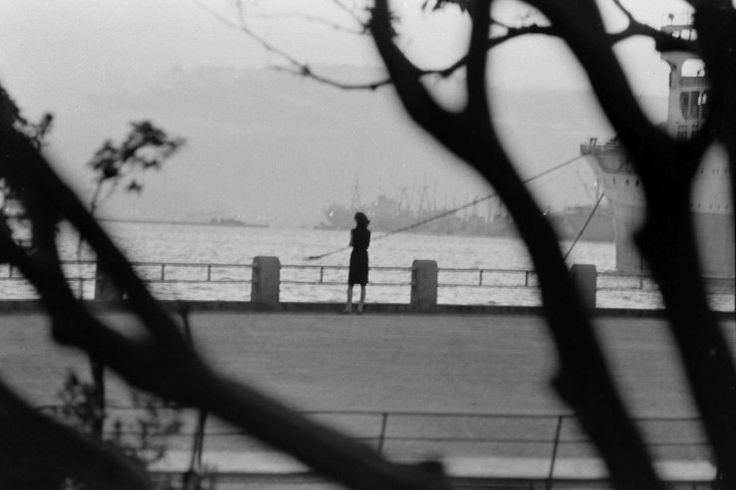 """TEENAGE WASTELAND: JAPANESE YOUTH IN REVOLT, 1964 — Michael Rougier — Not published in LIFE. """"Sometimes [Yoko] goes down to the port in Yokohama to watch the ships sail off to the places she only wishes she cold go. At sunset, her 'day' begins again."""""""