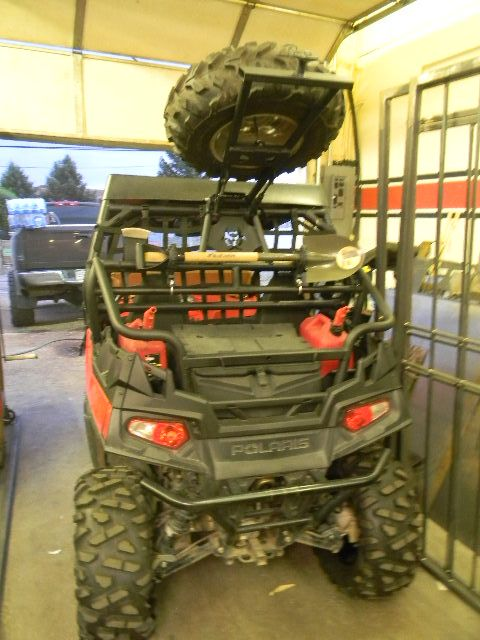 """Polaris RZR new custom designed CNC plasma cut front bumper, 2"""" lift, re designed, stock, rear cage with a liftable spring latched spare tire mount and shovel/axe rack.  All match with the BioHazard cut outs including the spare tire cover."""