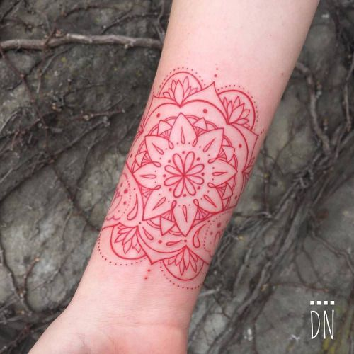 Red infinity mandala tattoo on Jens right inner wrist....