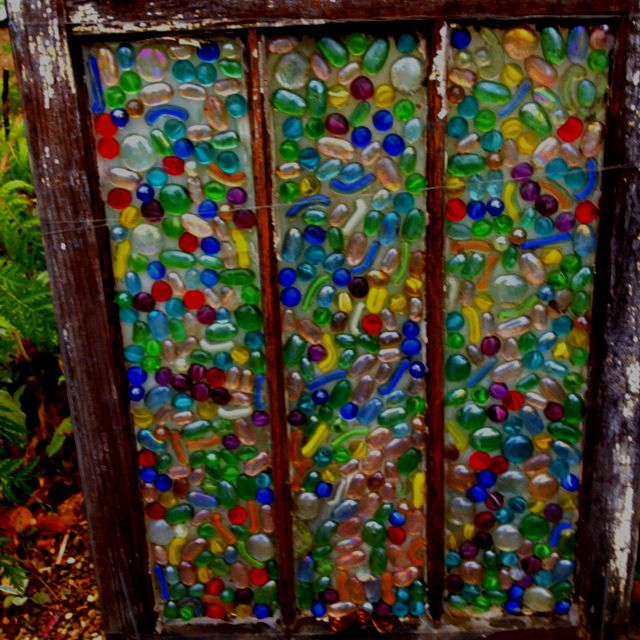 cover using a putty knife with clear caulk and apply flat glass marbles from the dollar store.. Display with a solar spotlight behind it!!