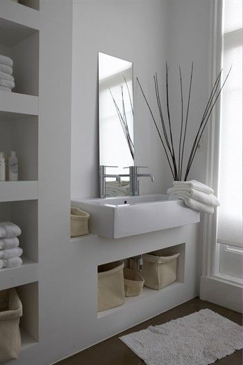 White-washed bathroom with sink and wall shelving, containing storage boxes and towels