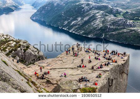 unidentified group of tourists enjoy breathtaking views from Preikestolen rock