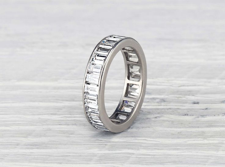 Antique Art Deco eternity band made in platinum and set with 27 emerald cut diamonds weighing approximately 4 carats total. Circa 1925. A little more presence than the average Deco band. An easy to we